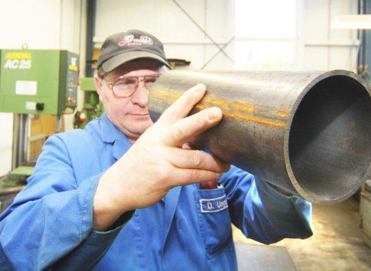 Mitarbeiter überprüft ein Metallrohr.