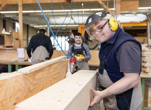 Mitarbeiter in der Tischlerei montiert Holzbretter.