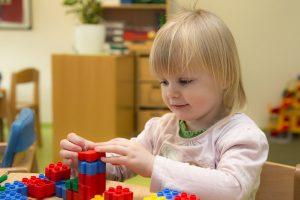 Kleine Mädchen sitzt an einem Tisch und spielt mit bunten Bauklötzen.