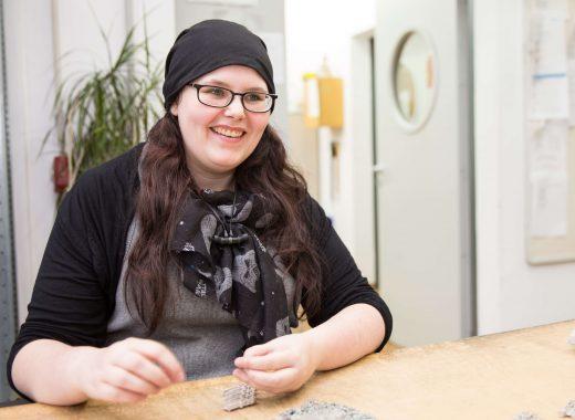 Junge Mitarbeiterin der E-Montage zeigt die Fertigung von Kabelbäumen