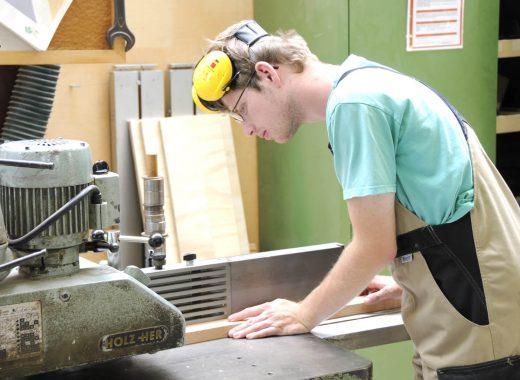 Foto: Junger Mann sägt Holzlatten zu