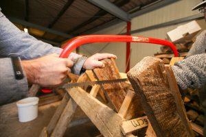 Foto: Ein Mann sägt Brennholz