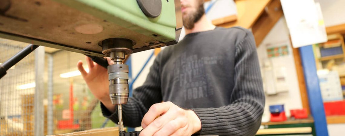 Foto: Mitarbeiter mit Bohrmaschine in der Werkstatt