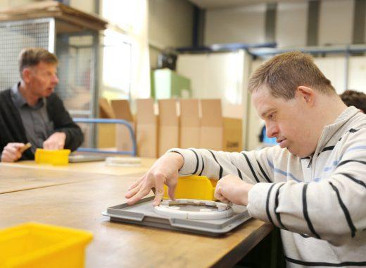 Foto: Mitarbeiter bei der Montage von Kunsstoffteilen