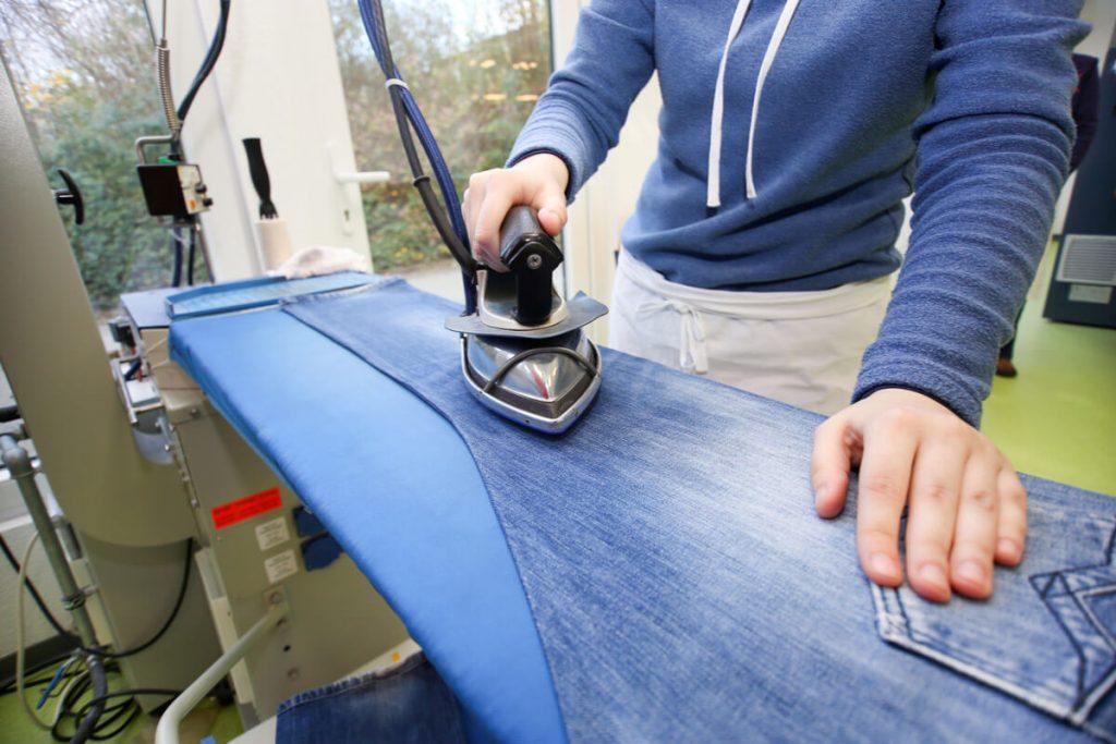Foto: Mitarbeiterin der Wäscherei beim Bügeln
